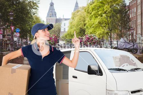 Composite image of happy delivery woman holding cardboard box and pointing up