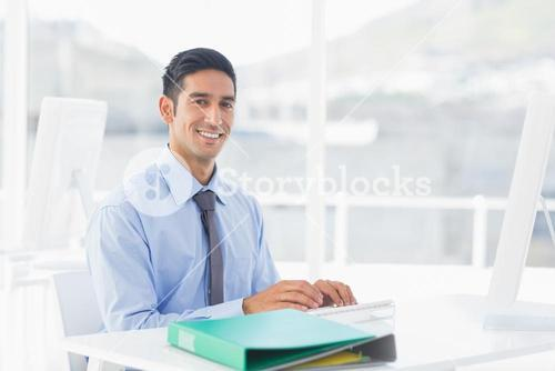 Smiling businessman using computer