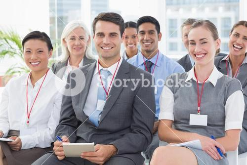Smiling business people looking at camera during meeting