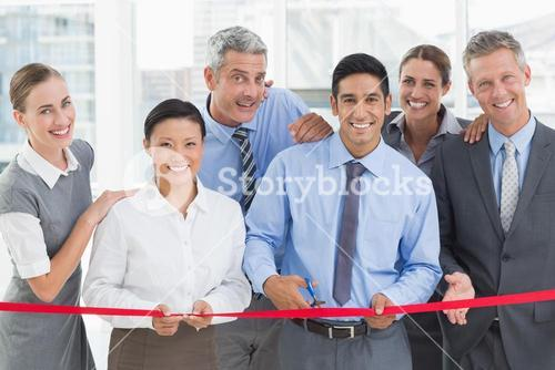 Business man cutting red strip