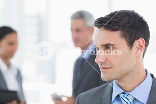 Businessman with colleagues behind