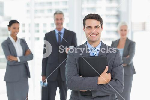 Businessman with colleagues behind in office
