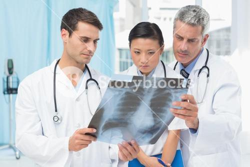 Male and female doctors examining x-ray