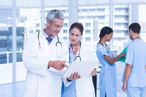 Male and female doctors working on reports
