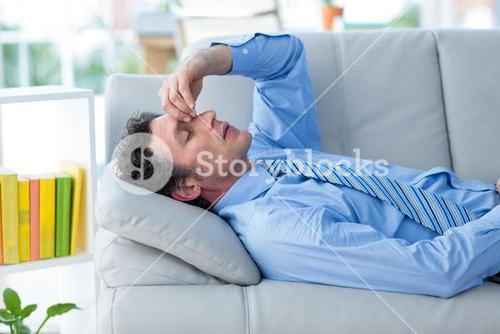 Worried businessman with head in hands lying on couch
