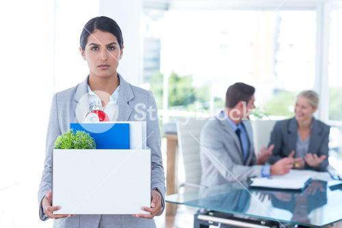 Businesswoman carrying her belongings in box