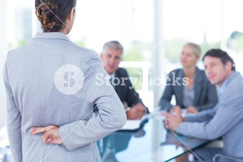 Businesswoman with fingers crossed behind her back