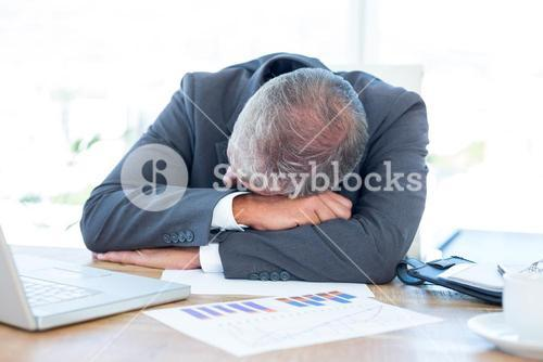 Tired businessman resting on desk