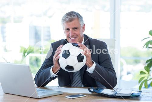 Smiling businessman holding soccer ball