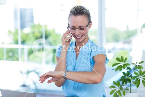 Smiling businesswoman having a phone call and checking time