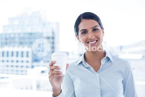 Smiling businesswoman holding disposable cup