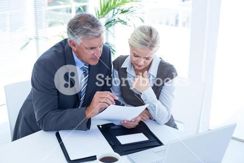 Businessman with secretary checking file