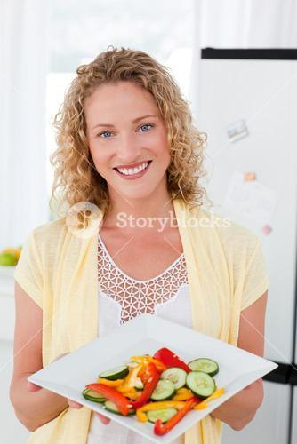 Woman showing her healthy food in her kitchen