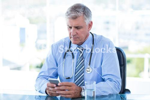 Serious doctor texting with his mobile phone