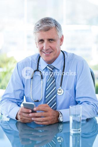 Smiling doctor texting with his mobile phone