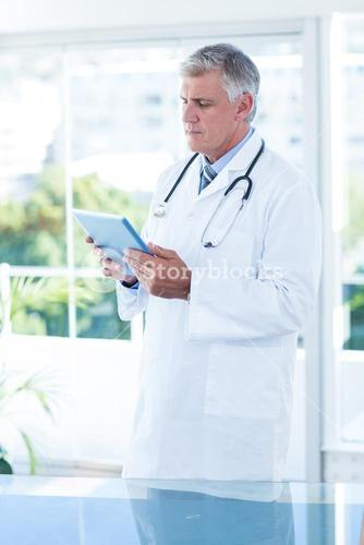 Concentrated doctor holding tablet