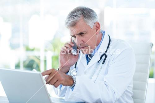 Serious doctor working on laptop and having phone call