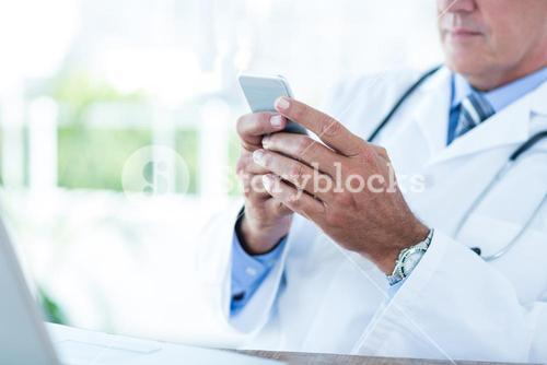 Doctor sitting at his desk and texting