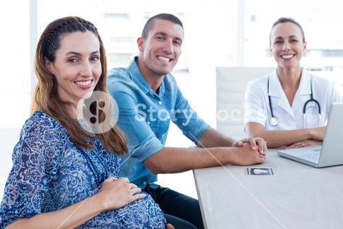 Doctor and future parents smiling at camera