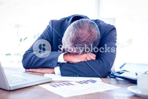 Businessman resting head on desk