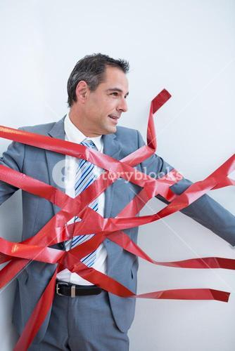Businessman trapped by red tape
