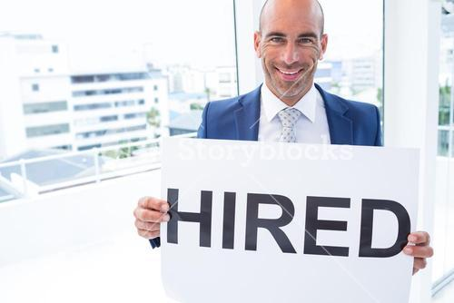 businessman holding a hired sign