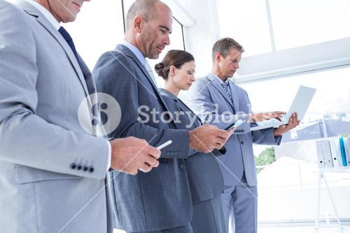 Business colleagues using their multimedia devices