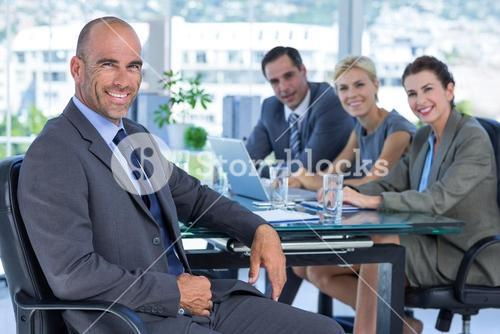 Businessman with his colleagues behind