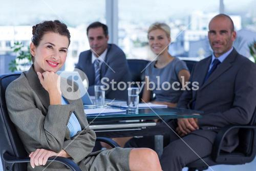 Businesswoman with her colleagues behind