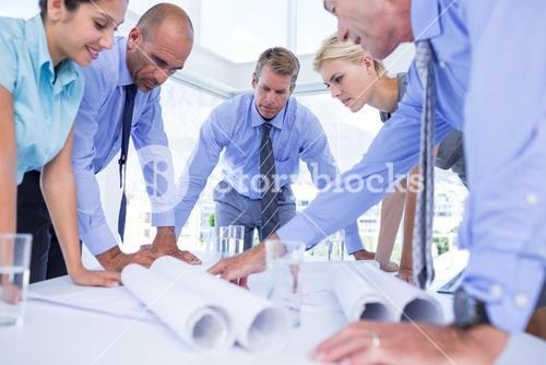 team of business people looking at construction plan