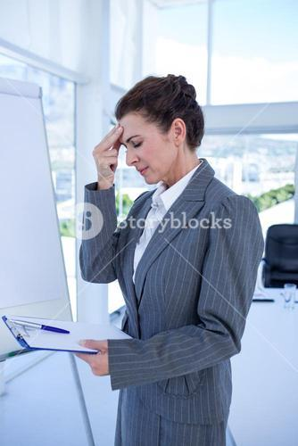 Irritated businesswoman looking at clipboard