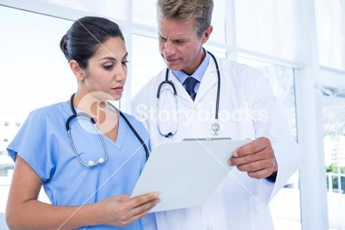 Serious doctors looking at clipboard