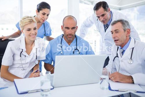 Teams of doctors working on laptop computer