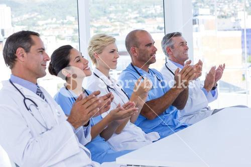 Team of doctors applauding during meeting