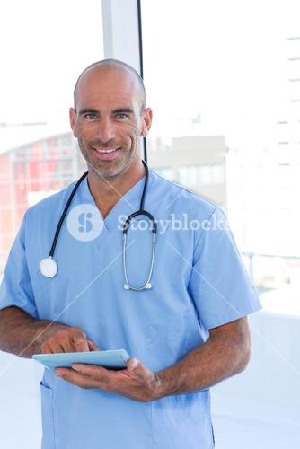 Smiling doctor using tablet computer