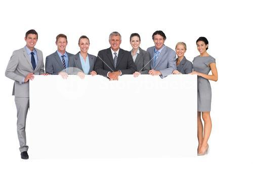 Smiling business team holding poster