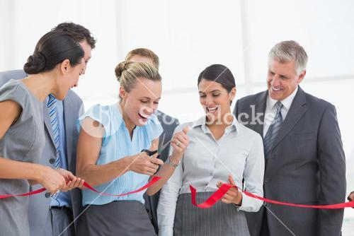 Happy business team cutting red ribbon