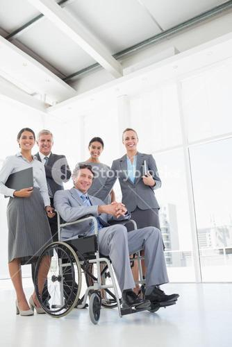 Disabled businessman with his colleagues smiling at camera