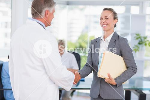 Confident doctor greeting pretty businesswoman