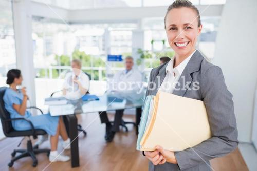 Smiling businesswoman holding files and looking at camera