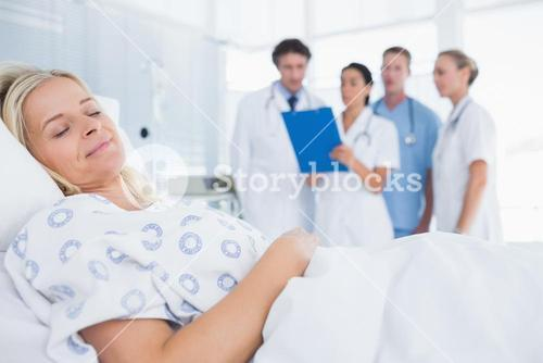 Sleeping patient with doctors behind