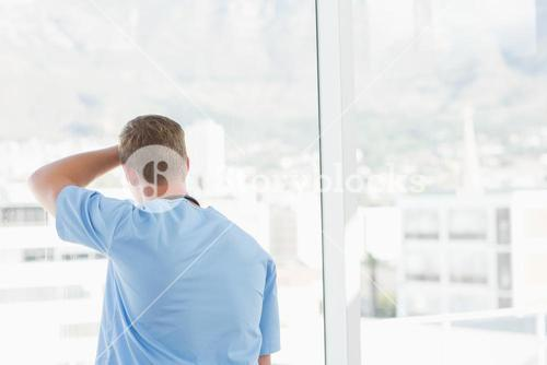 Male doctor looking through windows