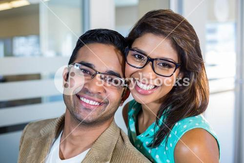 Happy couple embracing and looking at the camera