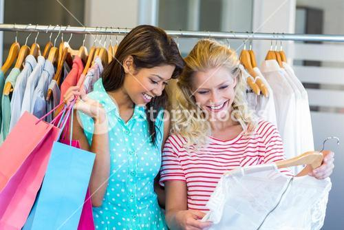 Smiling friends doing shopping together