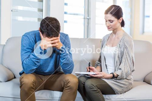 Psychologist talking with depressed man