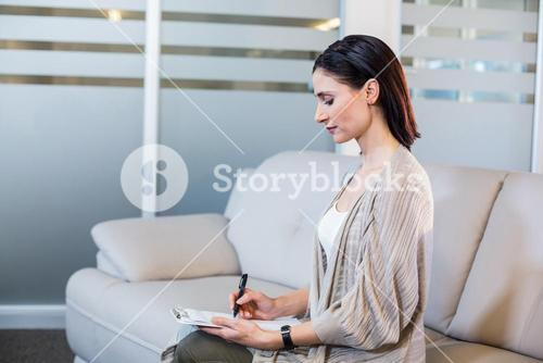 Psychologist sitting on the couch and taking notes