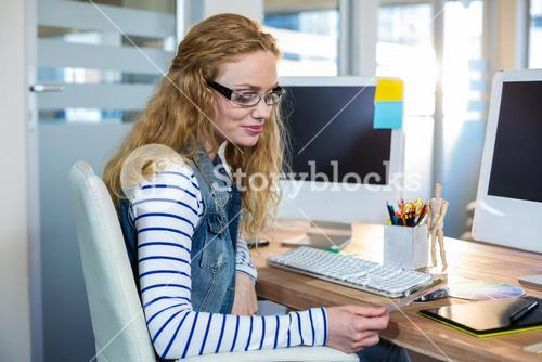Smiling designer sitting at her desk and looking at colour swatch