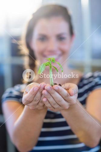 Brunette holding green sprouts