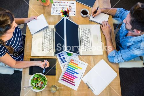 Partners working at desk using laptop