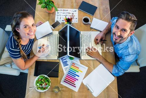 Smiling partners working at desk using laptop